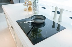 Frying pan on modern black induction stove, cooker, hob or built in cooktop with ceramic top in white kitchen interior