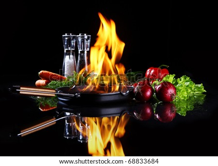 Frying pan with burning fire inside and fresh vegetables around