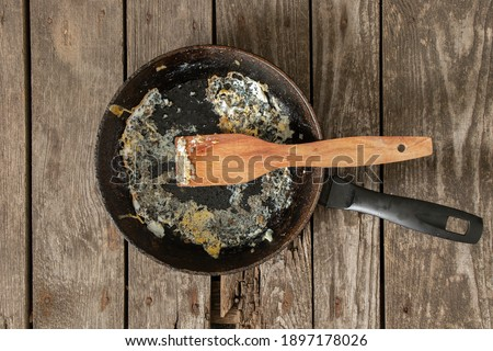 frying pan with food leftovers on a wooden table after breakfast in the kitchen at home Foto stock ©