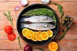 Frying pan with fresh seabass fish and ingredients on wooden background