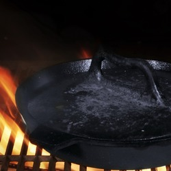 Frying Pan With Heavy Lid. Grill Pan On Hot Flaming BBQ Grate. Cast Iron Grill Pan With Gridiron, Closeup View.