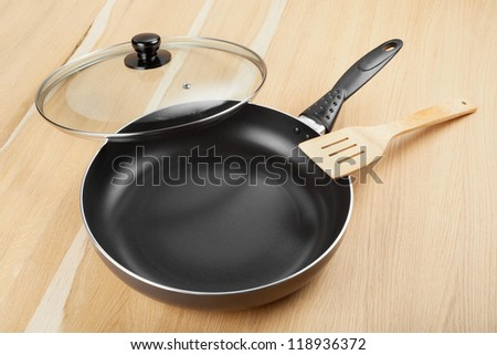 frying pan with lid on wooden table