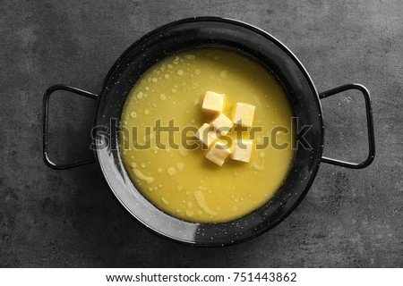 Frying pan with melting butter on grey background