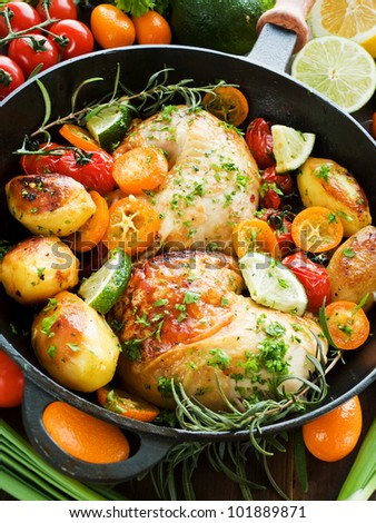 Frying pan with roasted chicken, vegetables, herbs and fruits. Shallow dof.