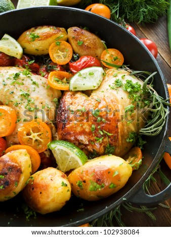 Frying pan with roasted chicken, vegetables, herbs and fruits. Viewed from above.