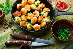 Frying pan with roasted tasty pelmeni.Fried dumplings
