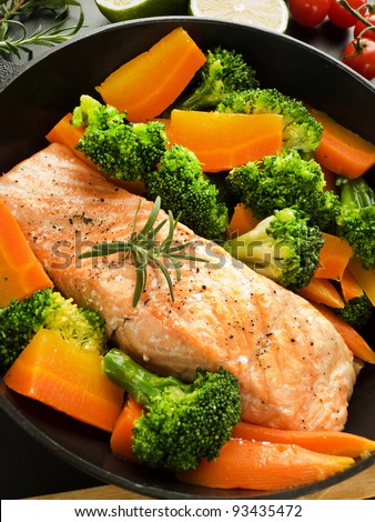 Frying pan with salmon steak, stir-fry veggies and herbs, Shallow dof.