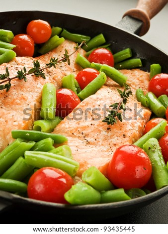 Frying pan with two salmon steaks, stir-fry veggies and herbs, Shallow dof.