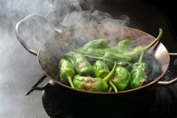 Frying peppers de padron or green pimientos in a steaming pan on a black stove. Traditional Spanish tapa or appetizer dish, copy space, selected focus, narrow depth of field