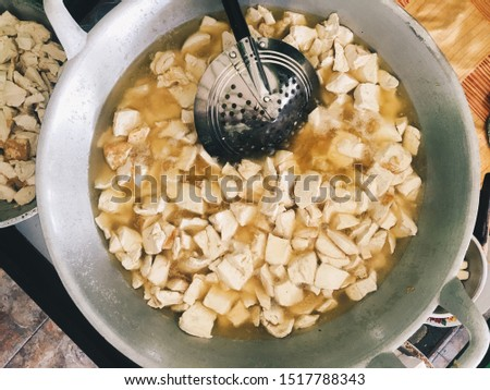 Frying White tofu in aluminum pan. Healthy food prepared in unhealthy burnt oil. Burnt oil in cooking pan. Traditional Market with food. #1517788343