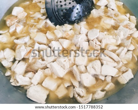 Frying White tofu in aluminum pan. Healthy food prepared in unhealthy burnt oil. Burnt oil in cooking pan. Traditional Market with food. #1517788352