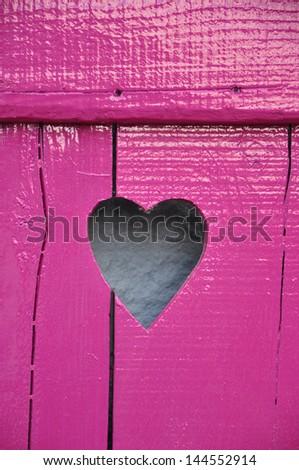 Fuchsine painted rough wooden window shutter with cut out Heart shape