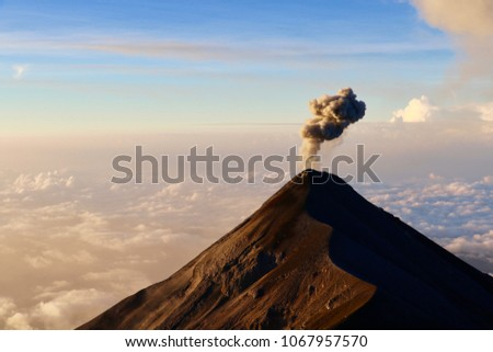 Fuego Volcano Erupting Red Hot Lava and Smoke into the Blue Sky above the Morning Clouds in Guatemala, as seen from Camp on Acatenango Volcano for Adventure Travel Hiking Trip