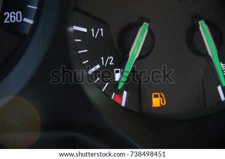 Fuel gauge with warning indicating low fuel tank, gas gauge indicating icon for gas station.
