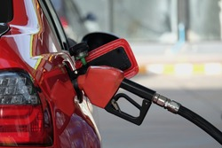 fuel nozzle filled car with fuel, car being filled gasoline at gas station