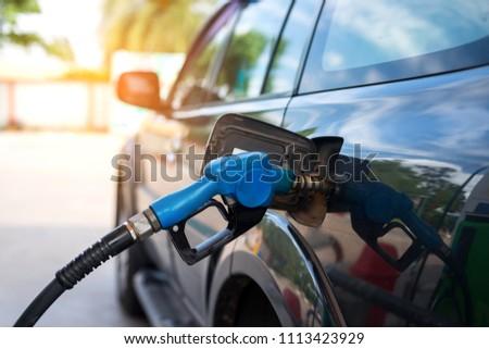 Fuel oil gasoline dispenser at petrol filling station.Holding fuel nozzle to refuel gasoline for car.