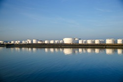 Fuel storage tanks and cranes at the port of Le Havre France