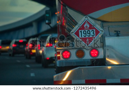 fuel tanker truck with safety flammable hazard sign 1993 in traffic on highway road at dusk