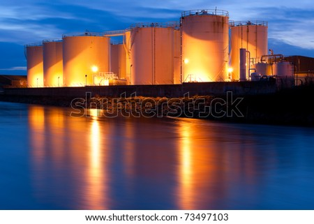 Fuel Tanks On The Bank Of The River  illuminated at night