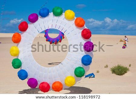 FUERTEVENTURA, SPAIN - NOVEMBER 09: Viewers watch from the ground as multicolored kites fill the sky at 25th International Kite Festival, November 9, 2012 in Dunes of Corralejo, Fuerteventura, Spain