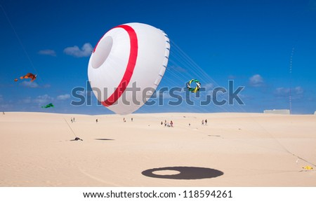 FUERTEVENTURA, SPAIN - NOVEMBER 10: Viewers watch from the ground as multicolored kites fill the sky at 25th International Kite Festival, November 10, 2012 in Dunes of Corralejo, Fuerteventura, Spain