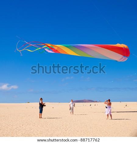 FUERTEVENTURA, SPAIN - NOVEMBER 13: Viewers watch from the ground as multicolored kites fill the sky at 24th International Kite Festival, November 13, 2011 in Dunes of Corralejo, Fuerteventura, Spain