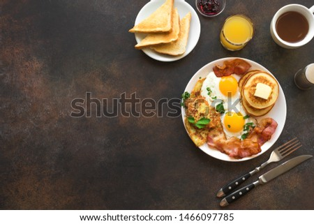Full American Breakfast on dark, top view, copy space. Sunny side fried eggs, roasted bacon, hash brown, pancakes, toasts, orange juice and coffee for breakfast.