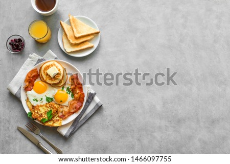 Full American Breakfast on gray, top view, copy space. Sunny side fried eggs, roasted bacon, hash brown, pancakes, toasts, orange juice and coffee for breakfast.
