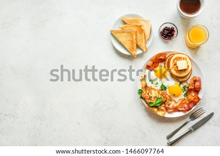 Full American Breakfast on white, top view, copy space. Sunny side fried eggs, roasted bacon, hash brown, pancakes, toasts, orange juice and coffee for breakfast.