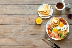 Full American Breakfast on wooden, top view, copy space. Sunny side fried eggs, roasted bacon, hash brown, pancakes, orange juice and coffee for breakfast.