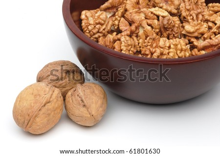 Full and cracked walnuts in bowl on white background