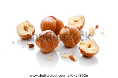 Full and halfs of hazelnuts on white background. Isolated