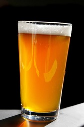 Full beer glass backlit with shadow on black
