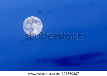 Full blue moon at blue sky background.