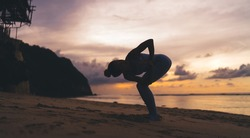 Full body barefoot faceless female in sportswear standing on sandy beach and practicing Revolved Chair pose on Bali during sunset