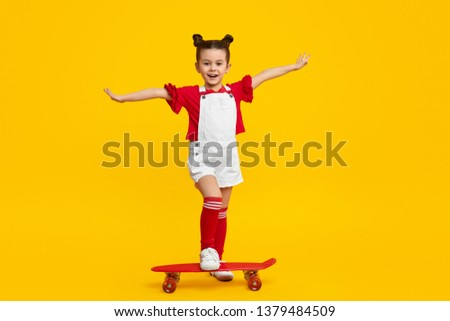 Full body cheerful little child in trendy outfit  stretching out arms and and stepping on modern skateboard against yellow background #1379484509