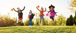 Full body children in spooky costumes and with trick or treat baskets jumping on green lawn during Halloween celebration in park