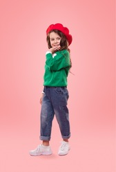 Full body confident smart child in trendy outfit posing for camera against pink background