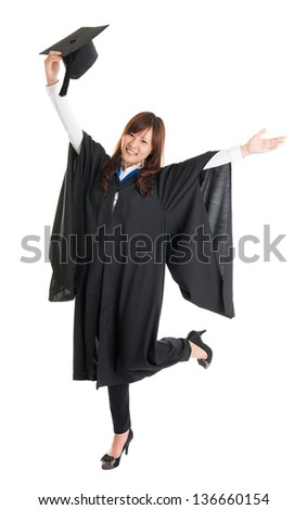 Full body excited Asian female student in graduation gown hands raised open arms jumping isolated on white background