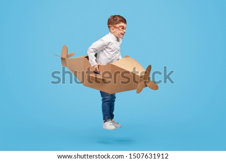 Full body excited little boy with cardboard plane smiling and jumping while imagining being pilot against blue background #1507631912