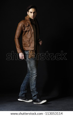 Full body fashion portrait of the young beautiful man over black background