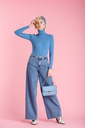 Full body fashion portrait of young elegant model wearing trendy wide leg jeans, light blue turtleneck, beret, holding small bag, posing on pastel pink background
