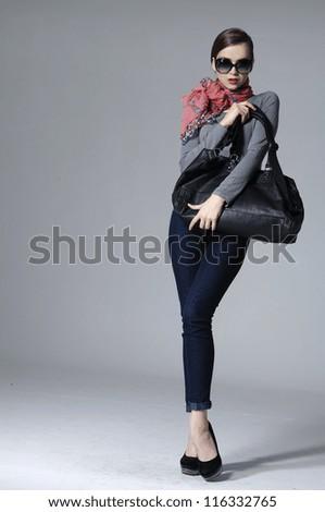 Full body fashion stylish girl with handbag posing on gray background