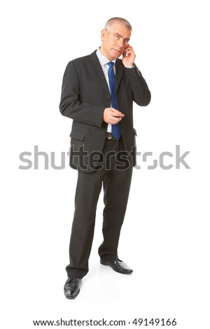 Full body image of mature standing business man wearing dark suit and talking on the mobile phone, isolated over white background