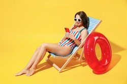 Full body length fun happy young woman wear red blue swimsuit sit on wooden chair hold use mobile cell phone isolated on vivid yellow color background studio Summer hotel pool sea rest sun tan concept
