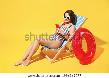 Full body length fun happy young woman wear red blue swimsuit sit on wooden chair hold use mobile cell phone isolated on vivid yellow color background studio Summer hotel pool sea rest sun tan concept Foto stock ©