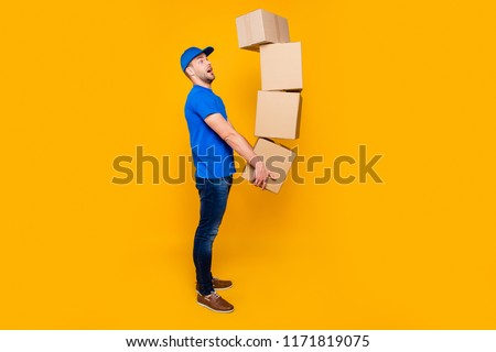 Full body length size, side profile view of handsome scared, shocked bearded deliver in uniform holding four large big flying up in air boxes in arms, isolated over bright vivid yellow background
