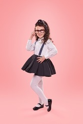Full body little girl in trendy outfit smiling for camera and adjusting glasses against pink background
