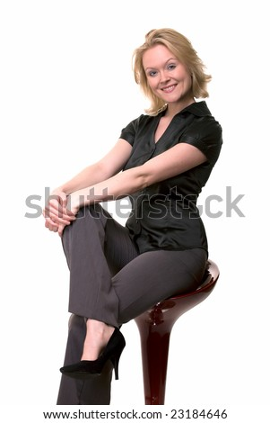 Full body of a blond woman wearing a black blouse and grey pants smiling sitting on a red bar stool with legs crossed
