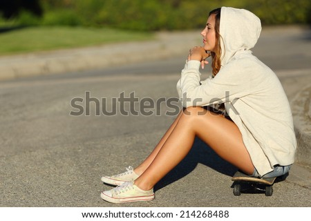 Full body of a profile of a pensive teenager girl sitting on a skate in the street looking away